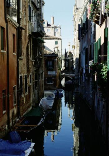 Nebenkanal mit alten Häusern und Booten in Venedig