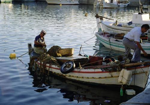 Fischer in ihren Booten beim Reparieren der Netze