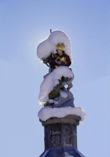Verschneiter Ortsbrunnen mit dem Heiligen St. Leonhard, Oberau, Oberbayern