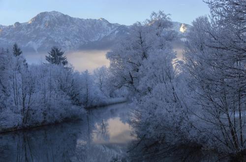 Verschneite Winterlandschaft an der Loisach am Kochelsee, im Hintergrund der Herzogstand; Bayern